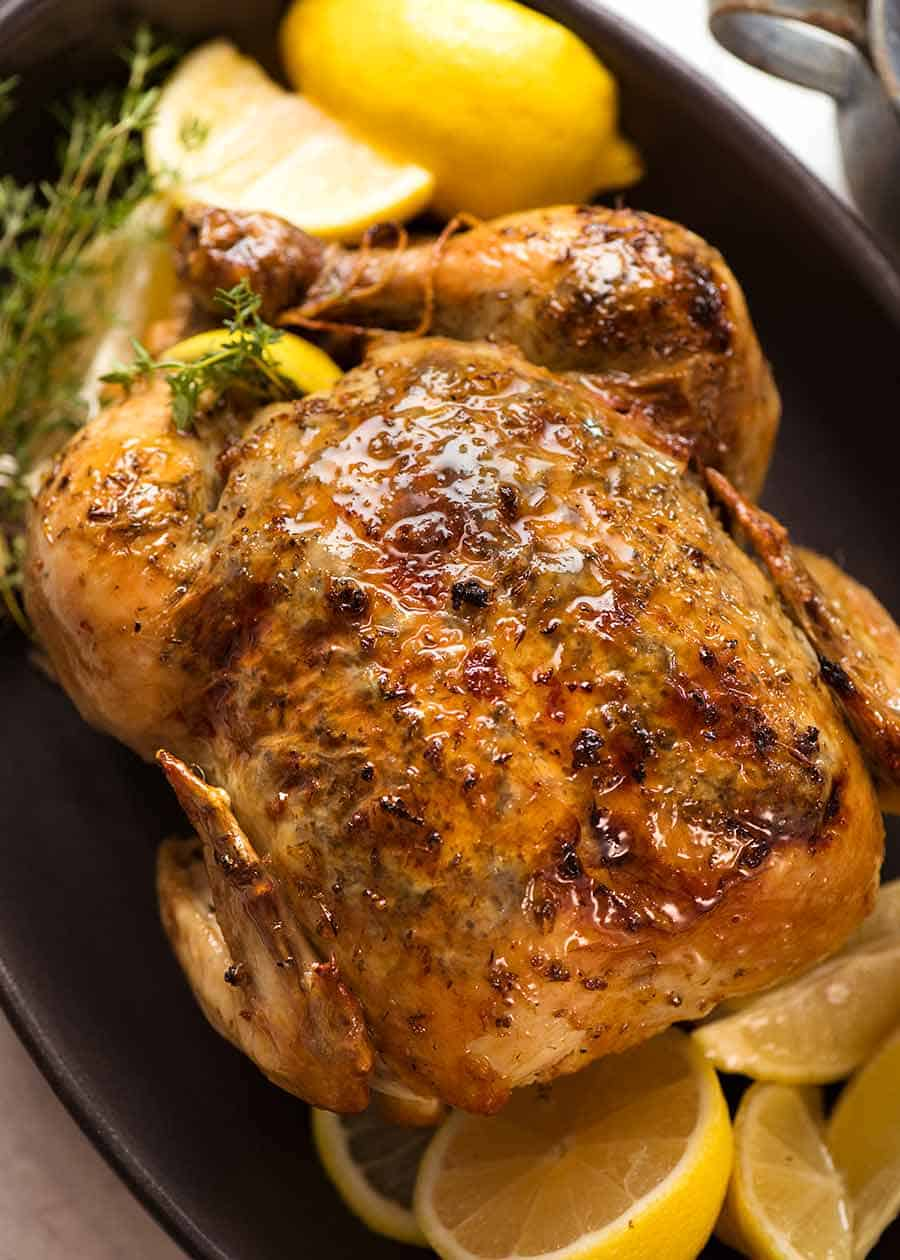 Overhead photo of Slow Cooker Roast Chicken (whole chicken) on a serving platter with lemon wedges, ready to be served
