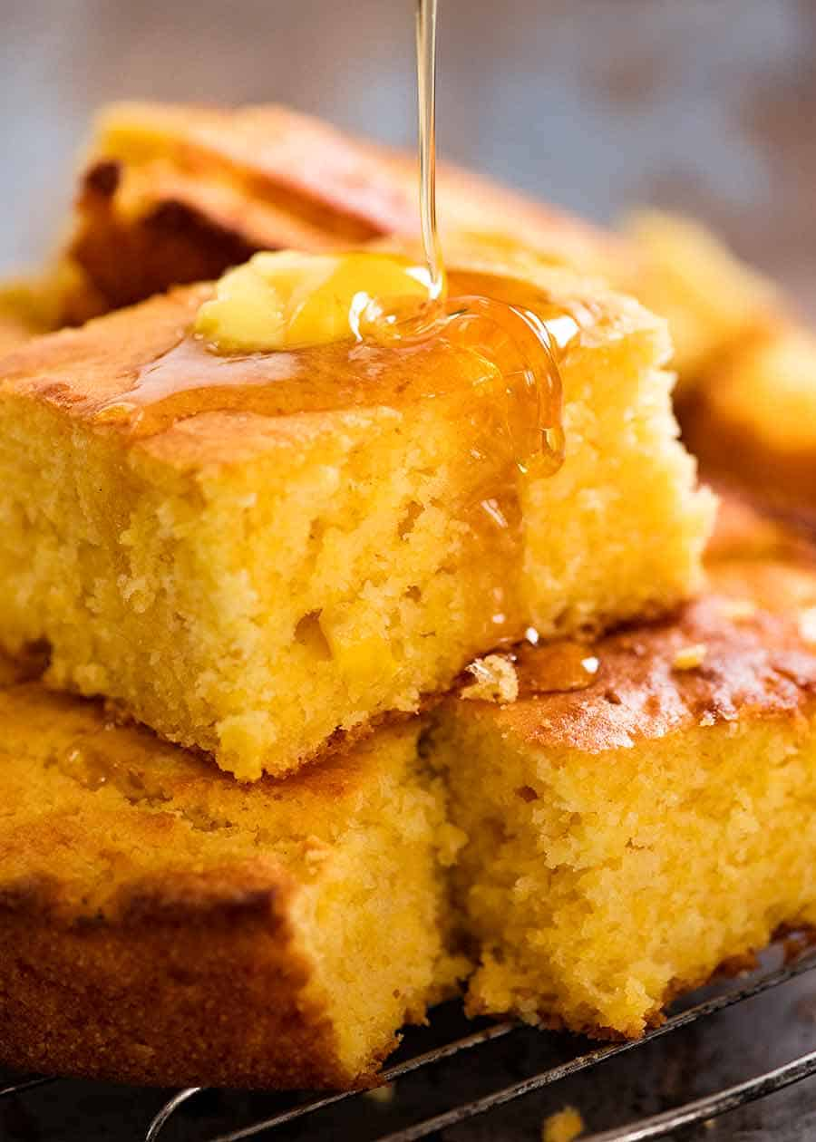 Honey being drizzled on a piece of Cornbread