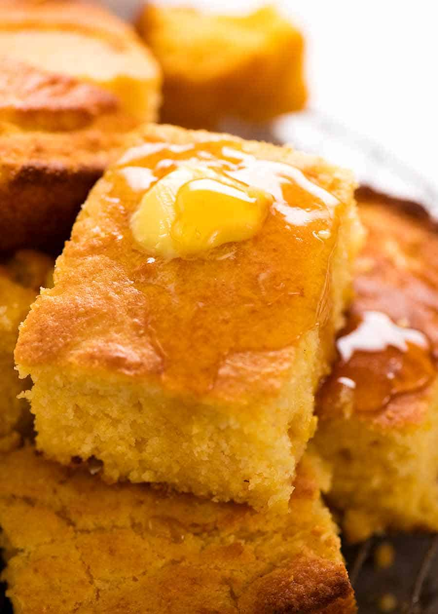 Close up of a piece of Cornbread with butter and honey
