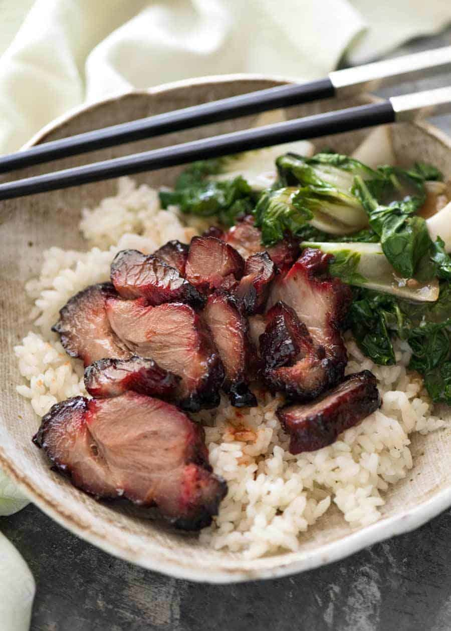 Char Siu (Chinese Barbecue Pork) served on rice with a side of steamed Chinese greens.