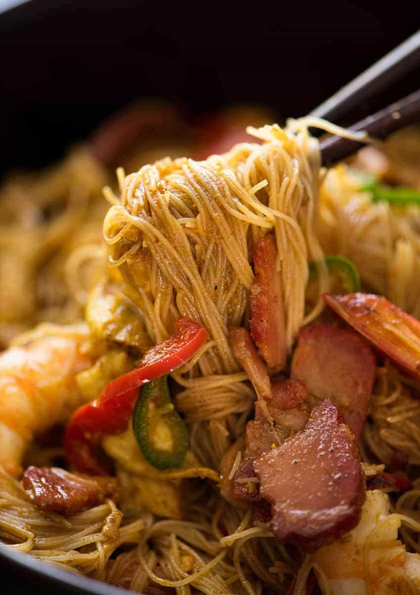 Close up of Char Siu Pork for Singapore Noodles being picked up with chopsticks