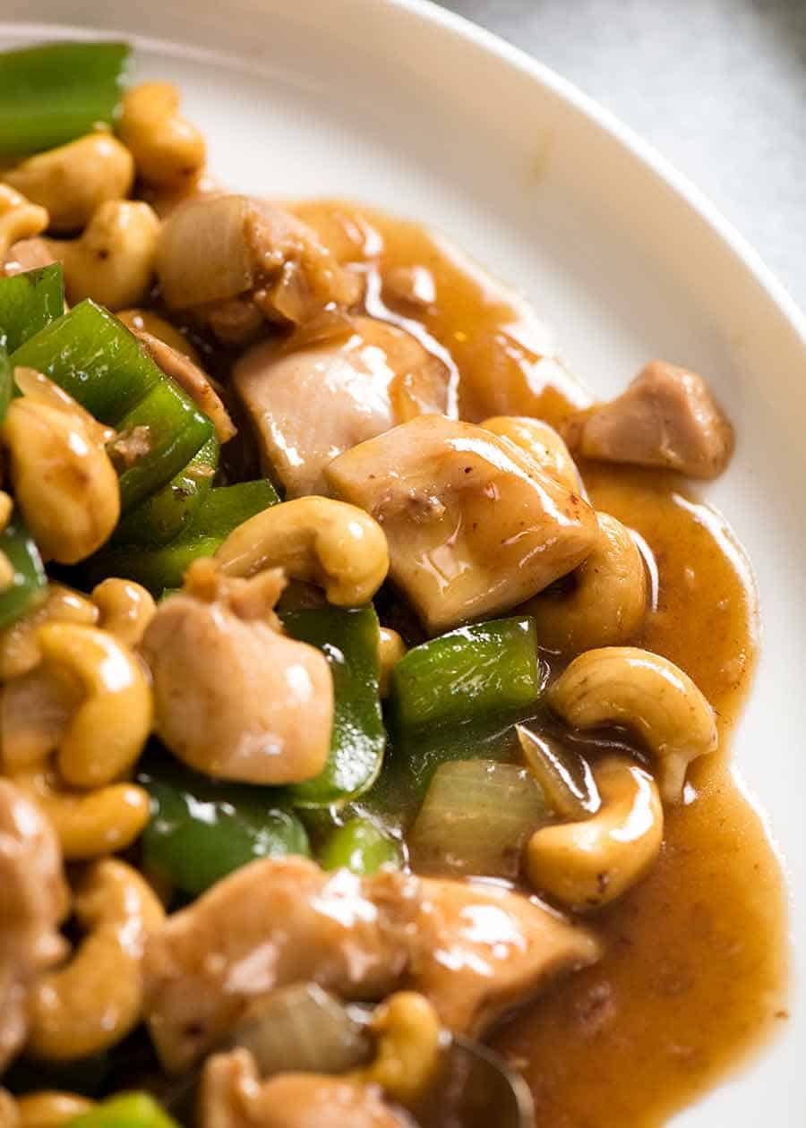 Close up of saucy Chinese Cashew Chicken on a white plate, ready to be served