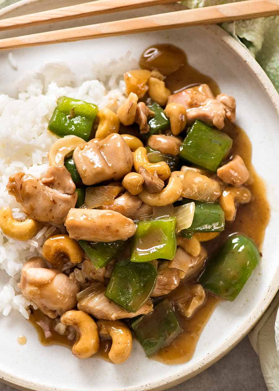 Chinese Cashew Chicken served on rice in a white bowl with chopsticks, ready to be eaten