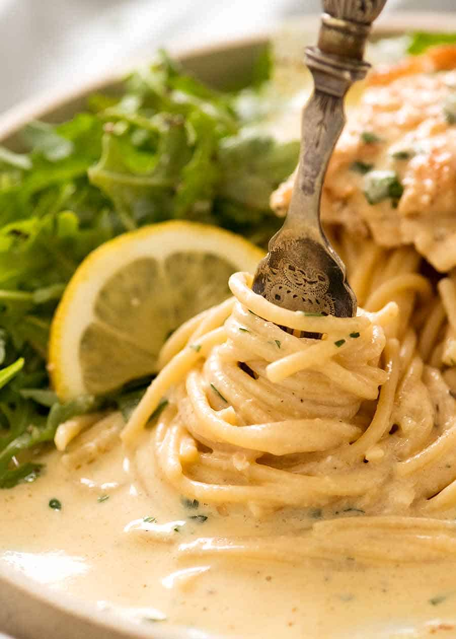 Fork twirling pasta coated with creamy lemon sauce from Creamy Lemon Chicken Breast