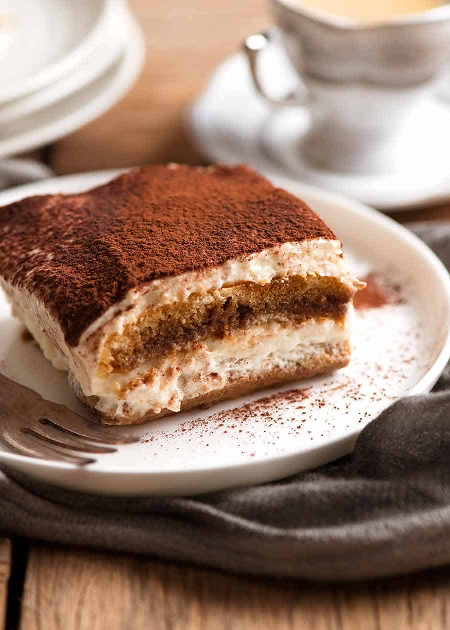 Close up of a slice of Tiramisu on a white plate, ready to be eaten