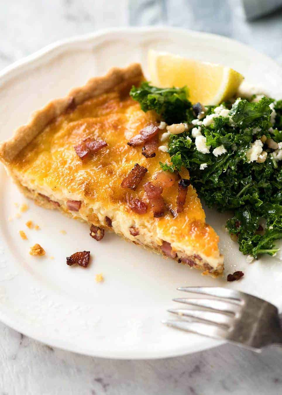 A slice of Quiche Lorraine on a plate, ready to be eaten.