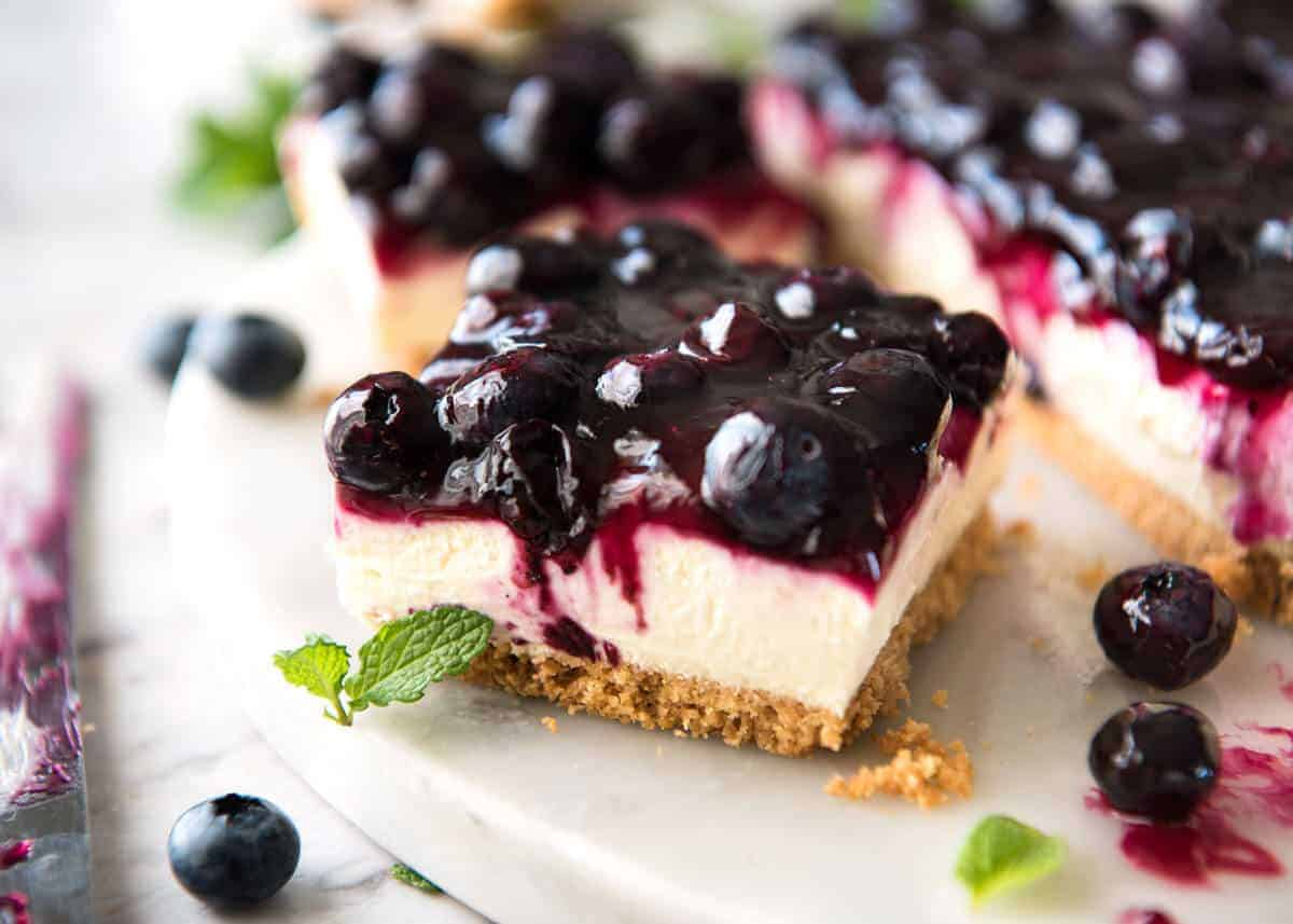 Easy and fast No Bake Blueberry Cheesecake Bars - creamy cheesecake with a gorgeous fresh blueberry sauce topping! www.recipetineats.com