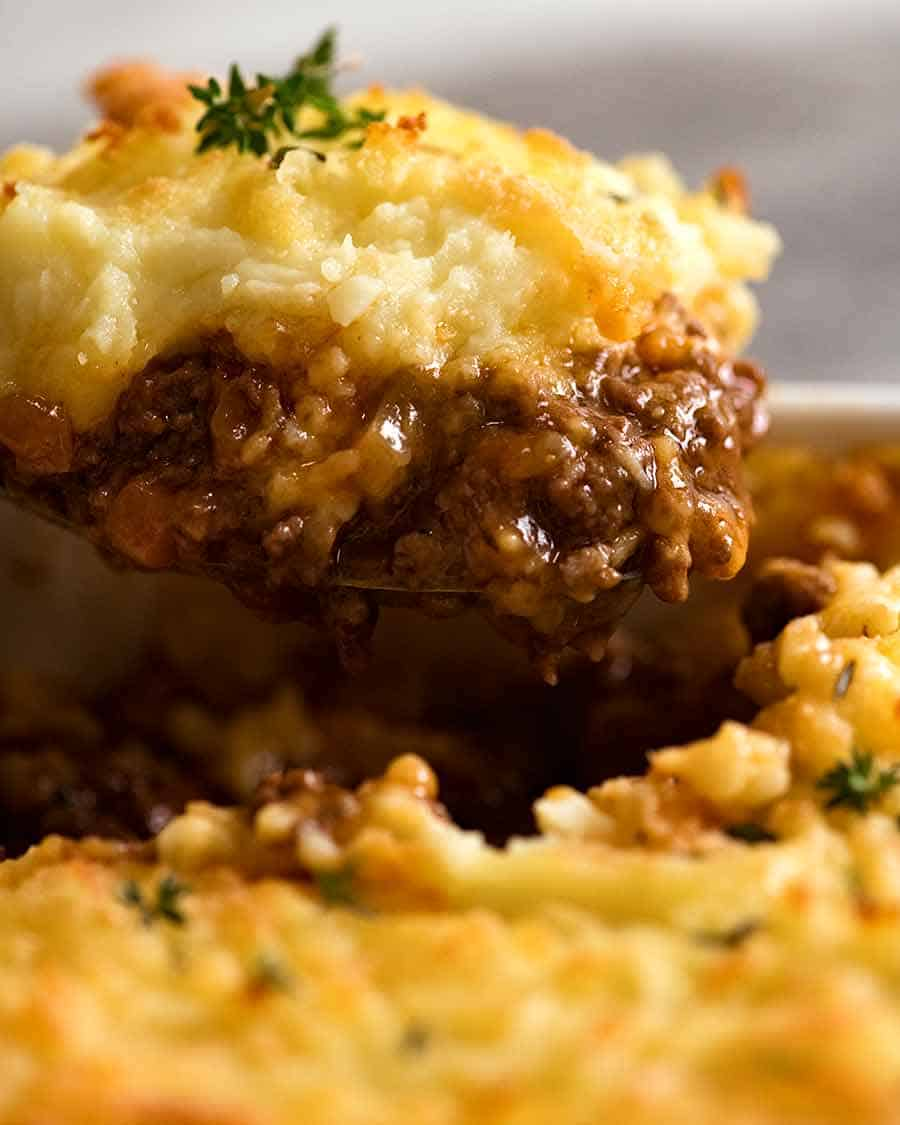 Close up of Cottage Pie being scooped out of baking dish, ready to be served