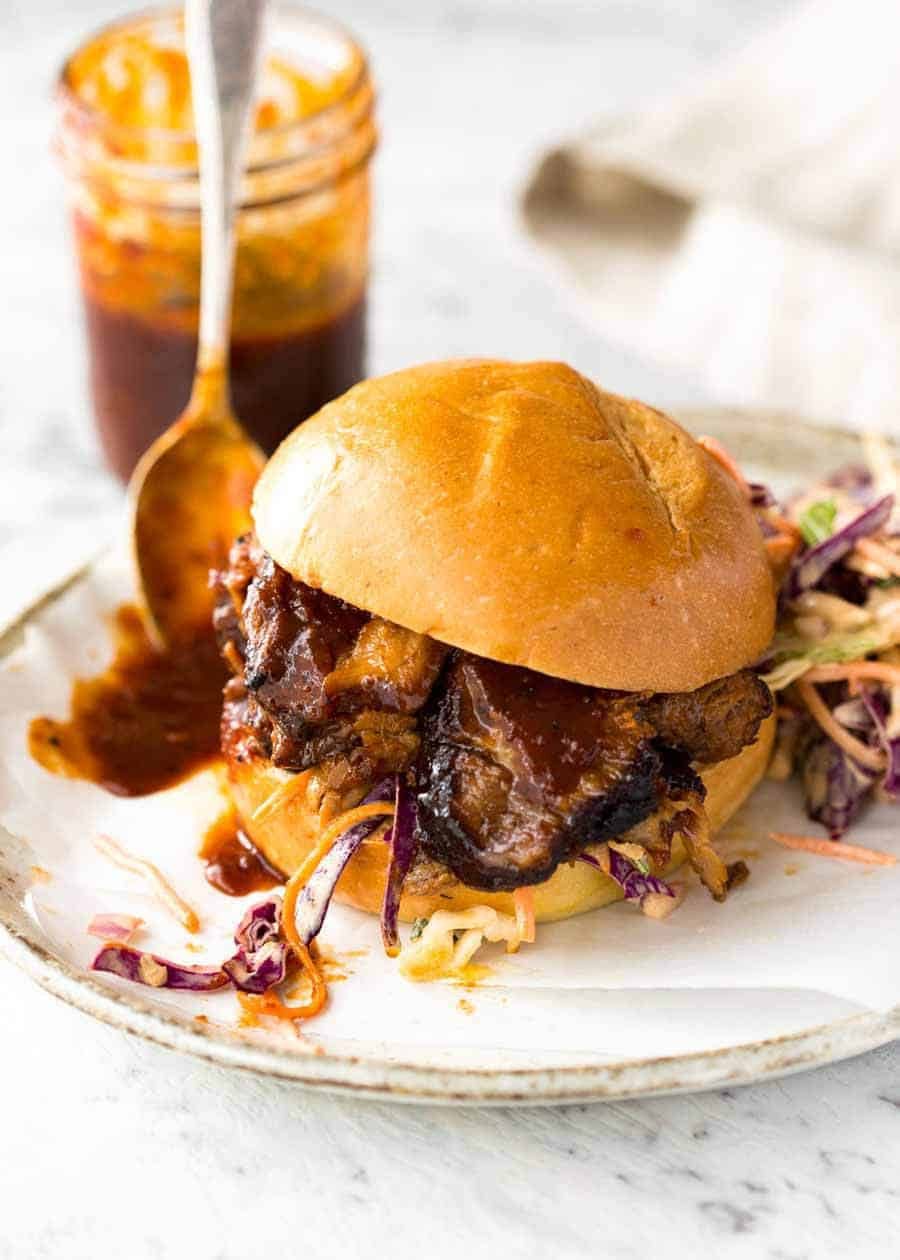 Slow Cooker Beef Brisket with BBQ Sauce on sliders on a white plate, ready to be eaten