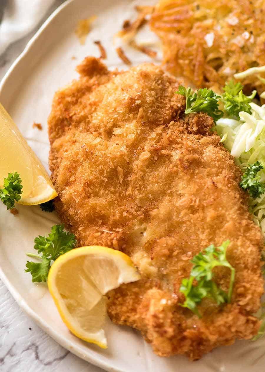 Overhead photo of crispy Schnitzel with lemon wedges