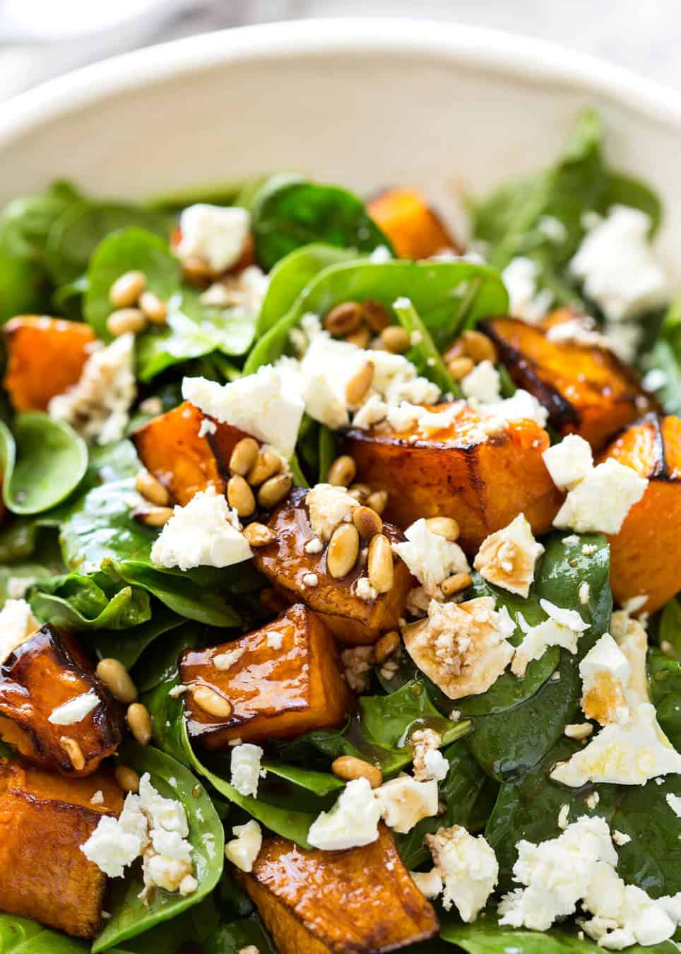 Close up of Roasted Pumpkin, Spinach and Feta Salad with Balsamic Dressing in a white salad bowl.