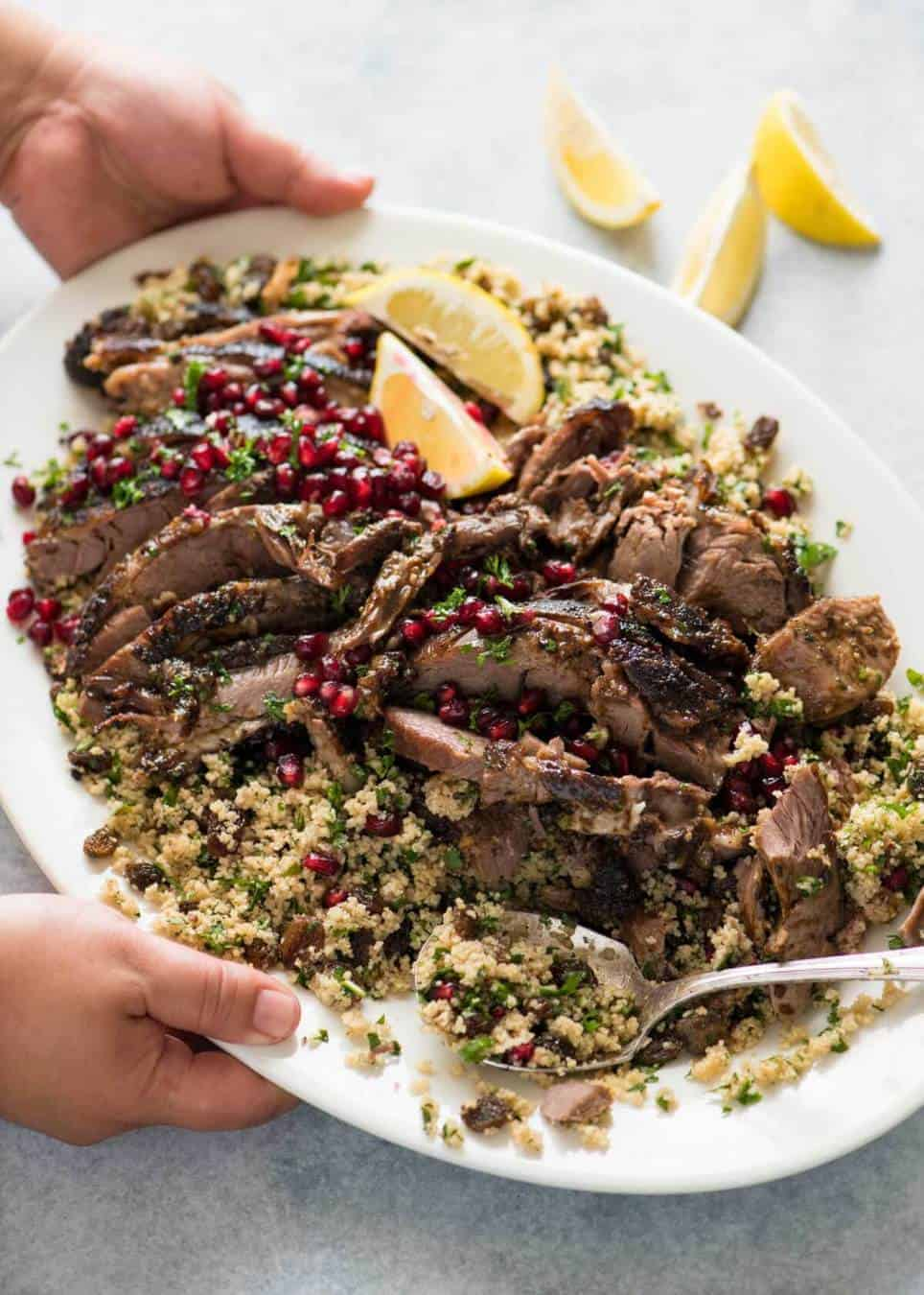 Tender slow cooked Lamb Shawarma cut into slices, piled on top of a herb couscous on a large white platter, garnished with pomegranate seeds and lemon wedges.