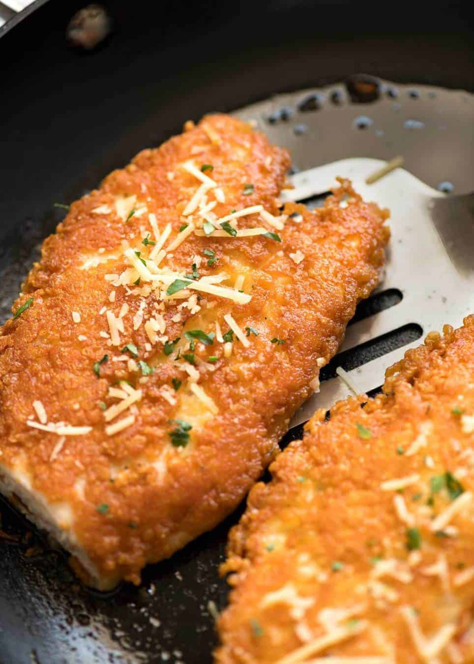Parmesan Crusted Chicken Breast being cooked in skillet.
