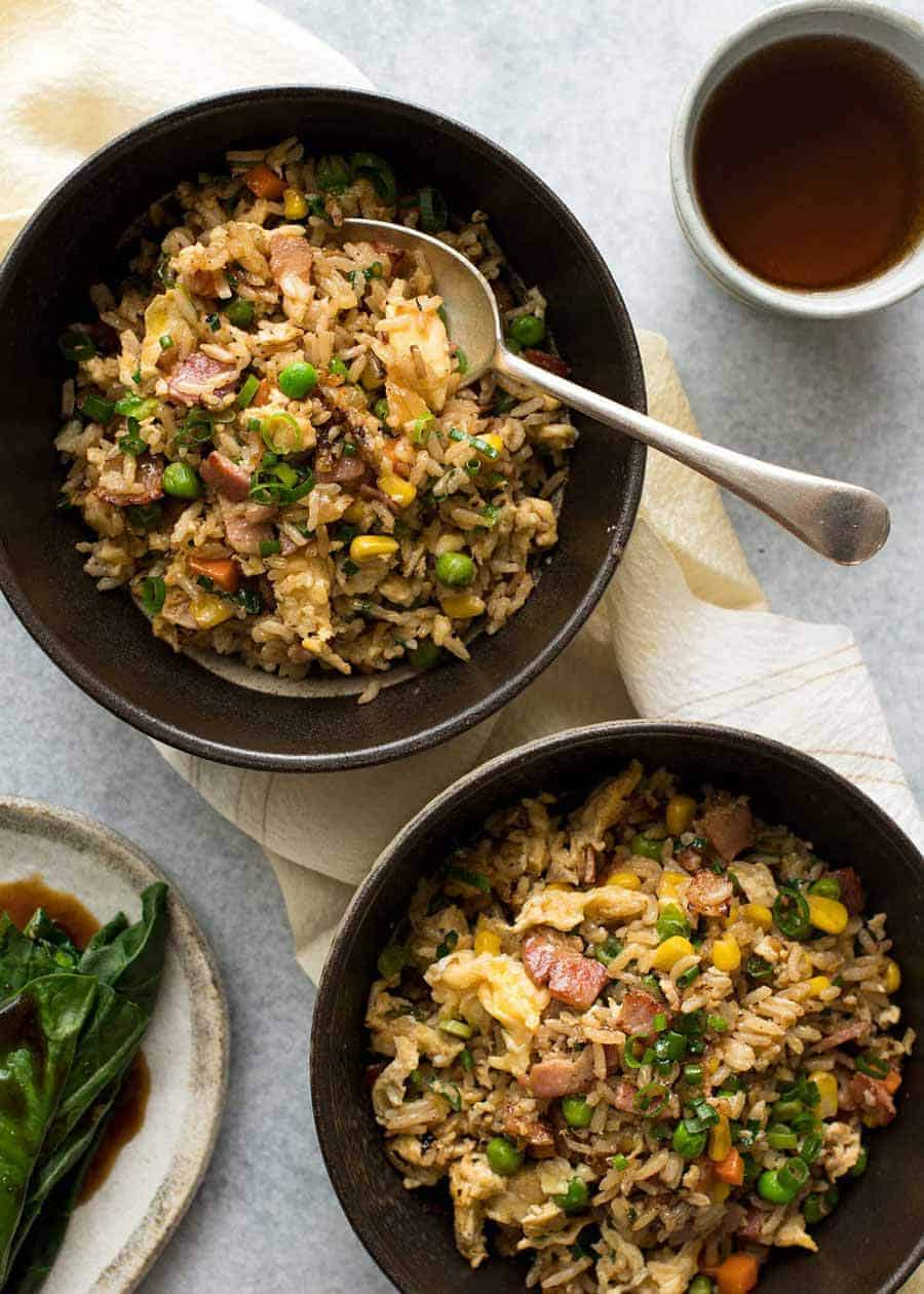 Overhead photo of 2 dark brown bowls with Egg Fried Rice, ready to be eaten
