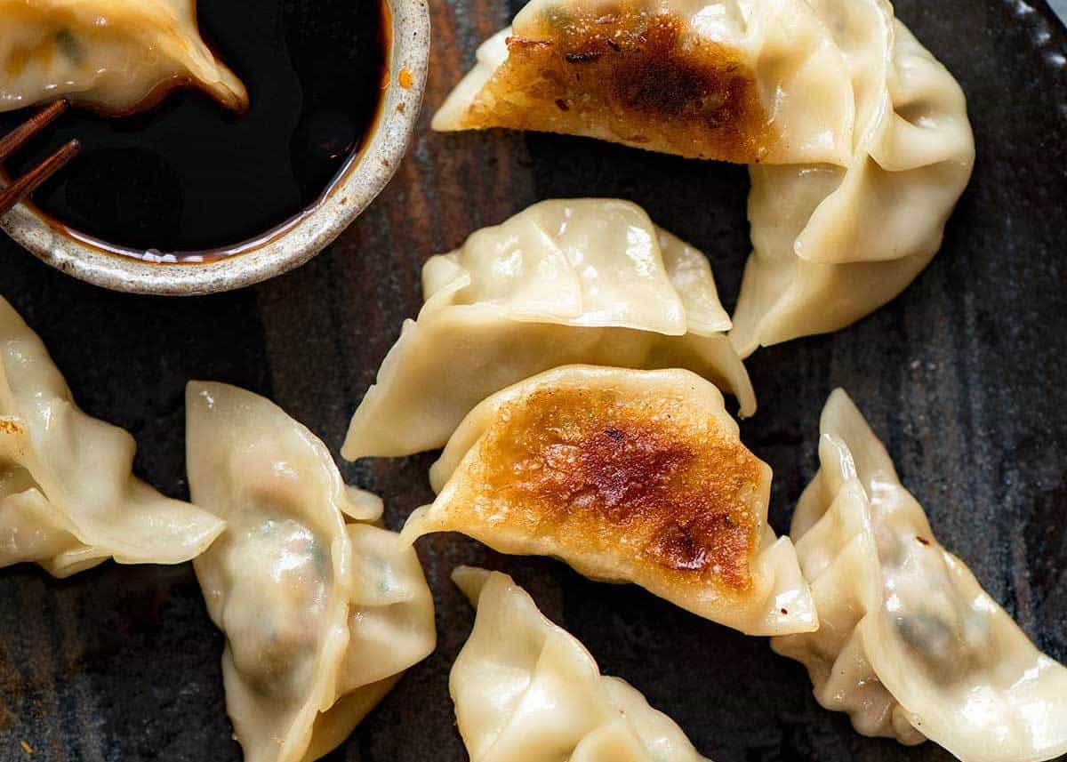 Overheat photo of Potstickers, also known as Pan Fried Chinese Dumplings, on a dark brown plate with dipping sauce.