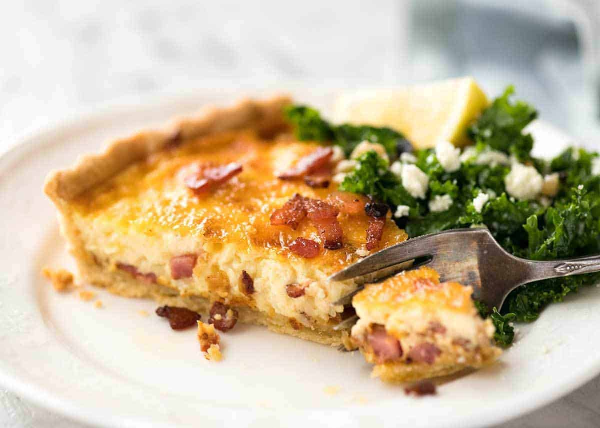 Slice of quiche lorraine on a white plate with a fork cutting into it