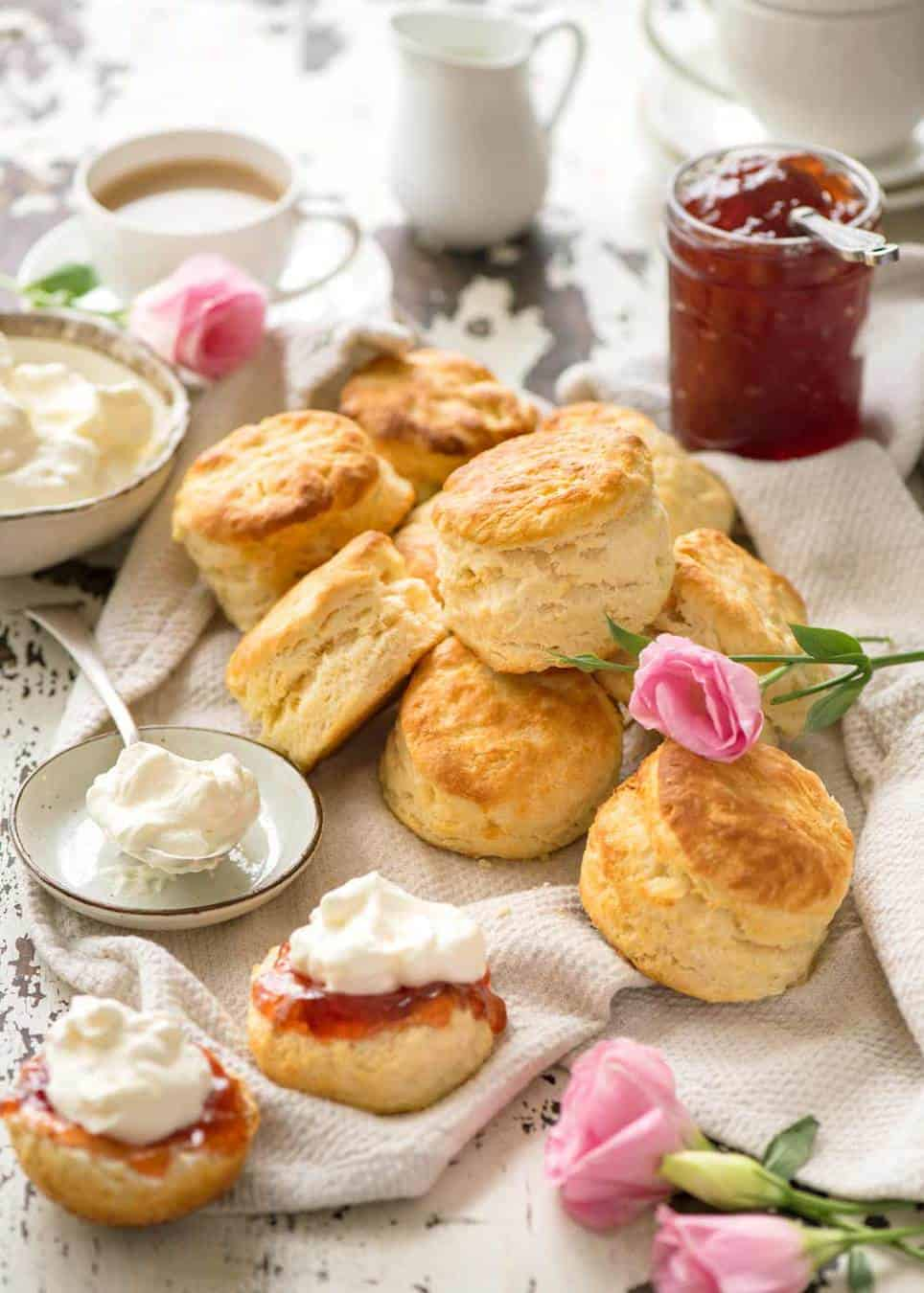 An afternoon tea with scones, jam and cream, with coffee and tea.