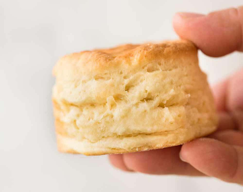 Close up of a plain golden scone being held by fingers.
