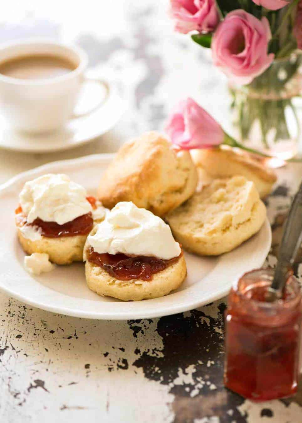Photo of plain scones on a small white plate with one split open, piled high with jam and cream, ready to be eaten.