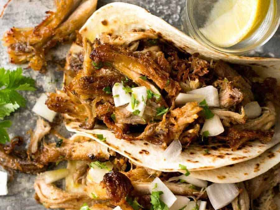Overhead photo of two Pork Carnitas Tacos with tequila shots on the side.