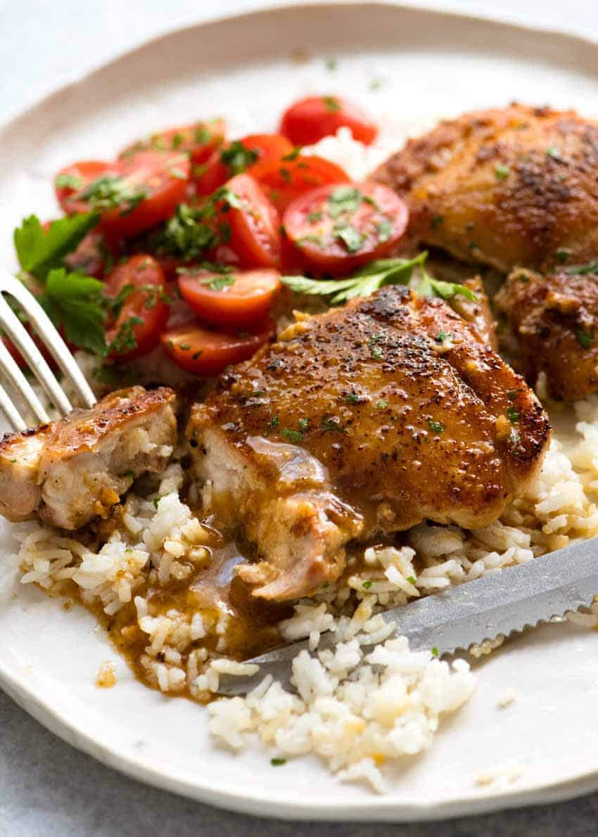 Garlic Chicken Thighs on a rustic cream plate, served over rice with a terrific quick and easy garlic butter sauce.