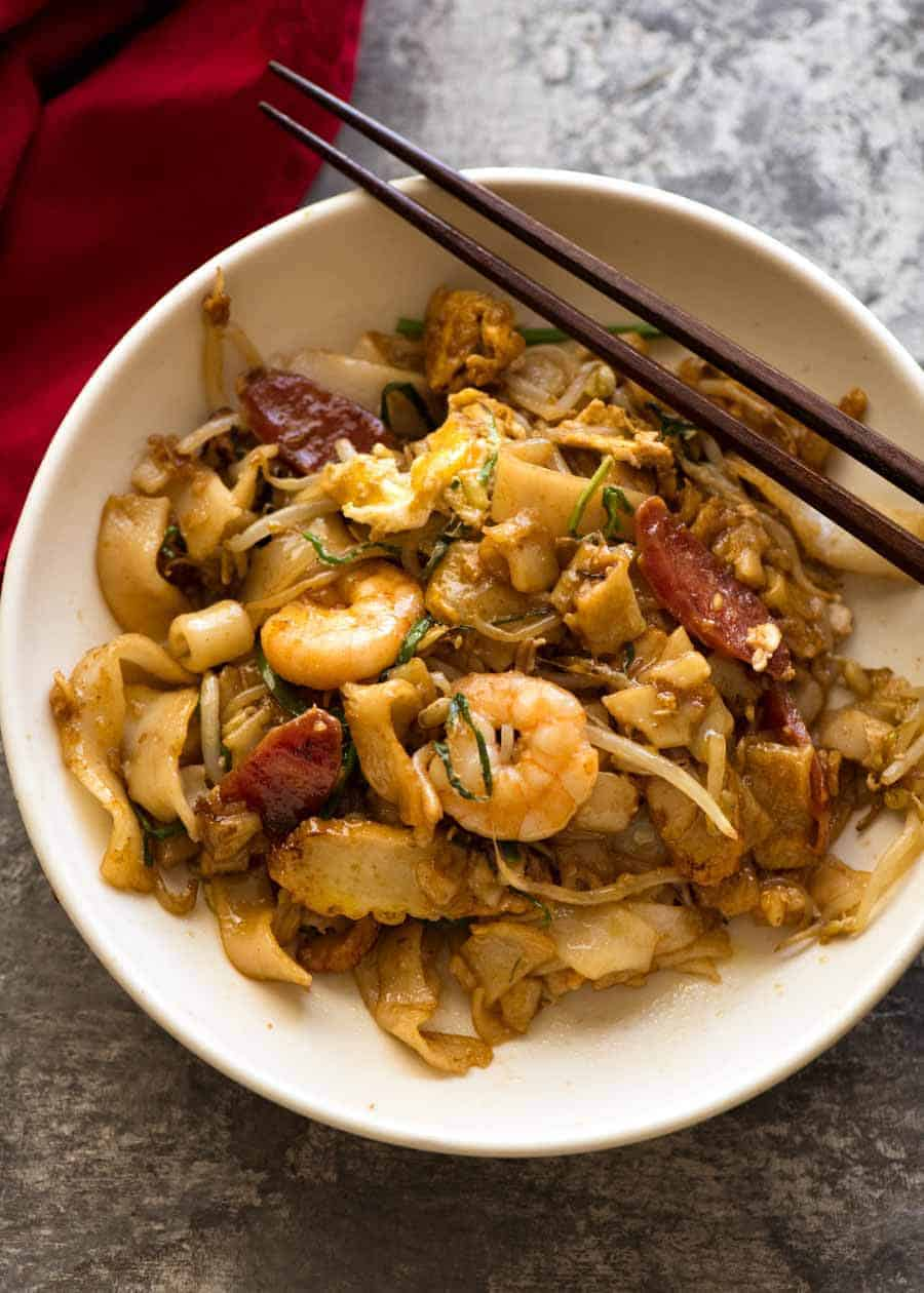 Char Kway Teow in a rustic white bowl with chopsticks resting on the side, ready to be eaten