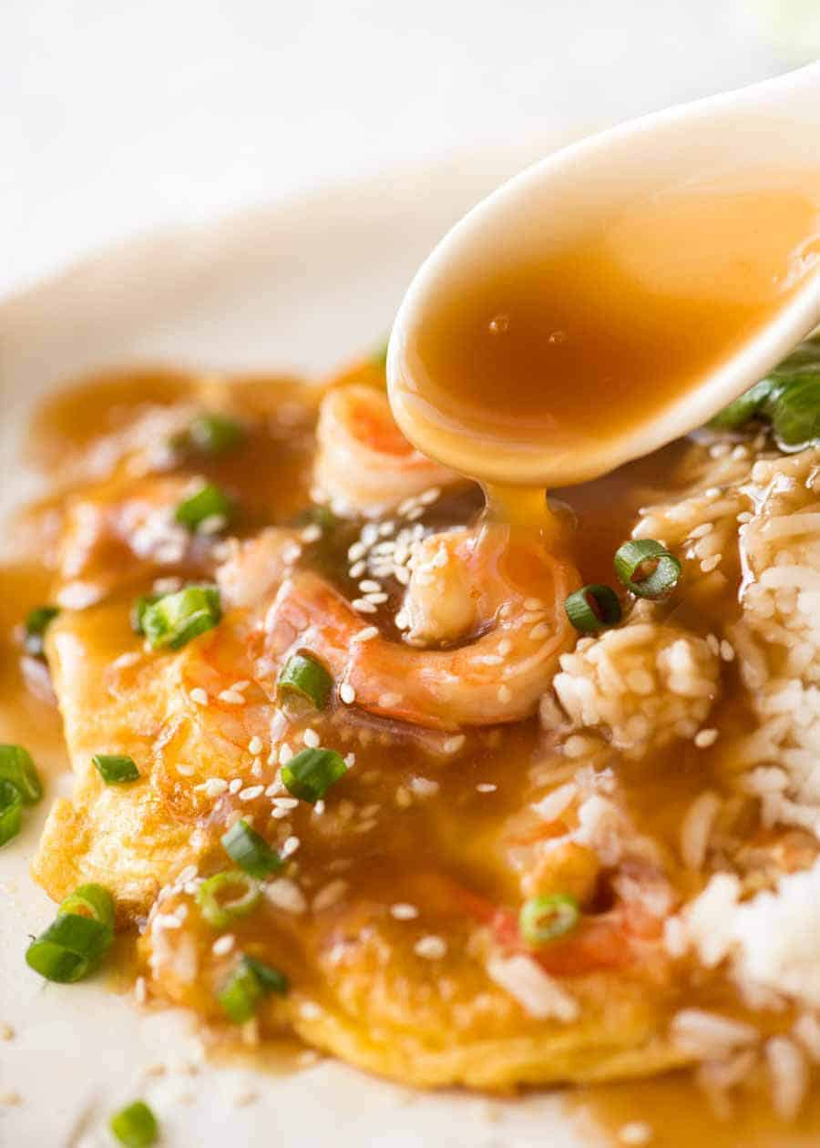 Spoon drizzling Chinese brown sauce over Egg Foo Young