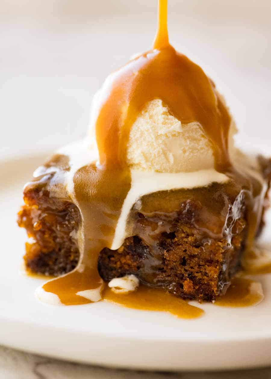 Warm butterscotch sauce being poured over Sticky Date Pudding topped with ice cream