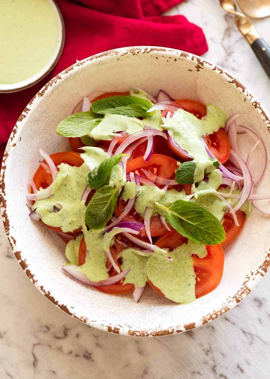 Indian Tomato Salad drizzled with Mint Dressing in a rustic cream bowl, ready to be served
