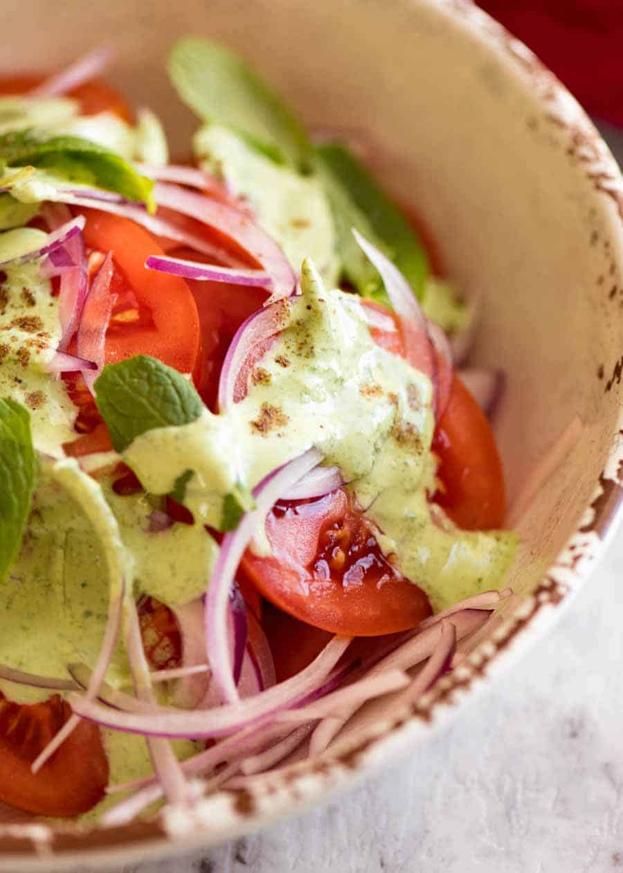 Close up of Indian Tomato Salad drizzled with Mint Dressing in a rustic cream bowl, ready to be served