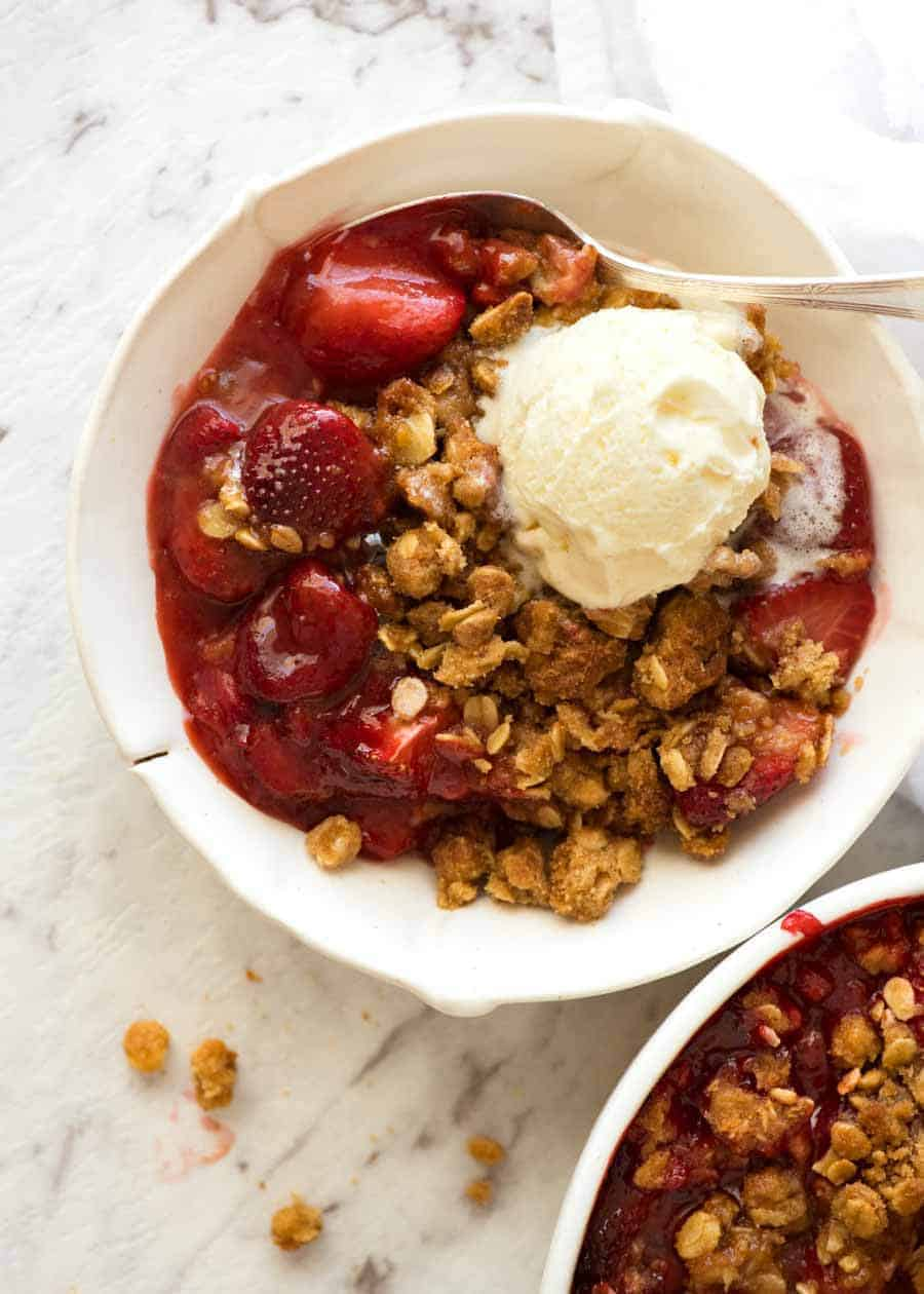 Overhead photo of Strawberry Crumble with vanilla ice cream in a rustic white bowl, ready to be eaten