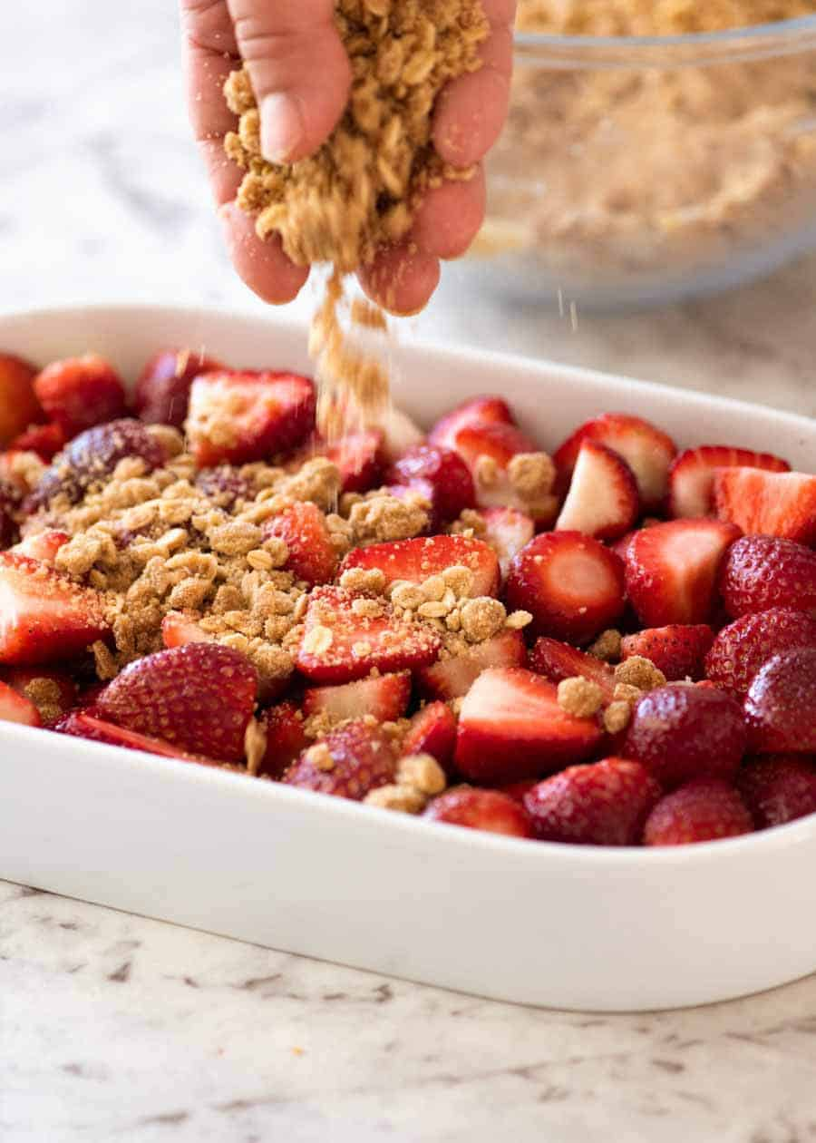 Sprinkling crumble topping on strawberries for Strawberry Crumble