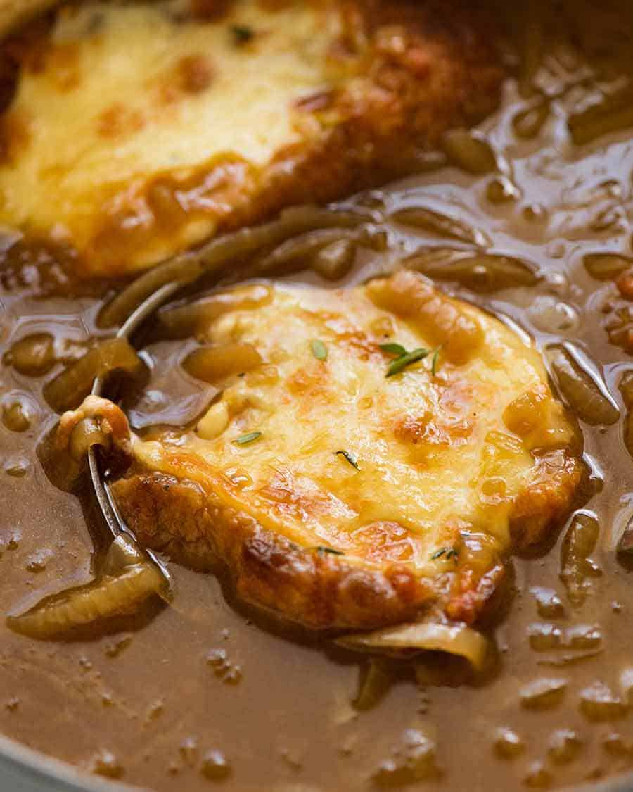 Close up of French Onion Soup being ladled out of pot