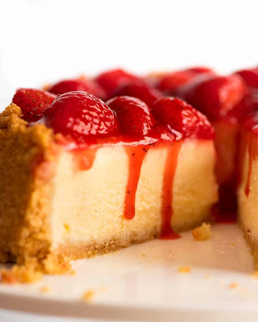 Close up of slice of Strawberry Cheesecake with Strawberry Sauce dripping down the side