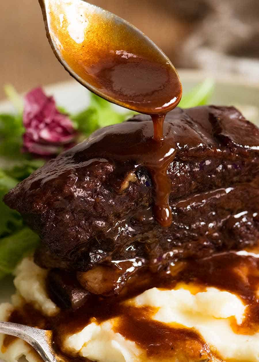 Spoon drizzling Red Wine Sauce over Slow Braised Beef Short Ribs