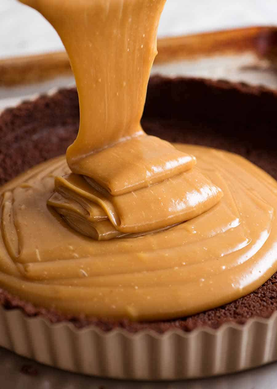 Peanut butter caramel filling being poured into cookie crust