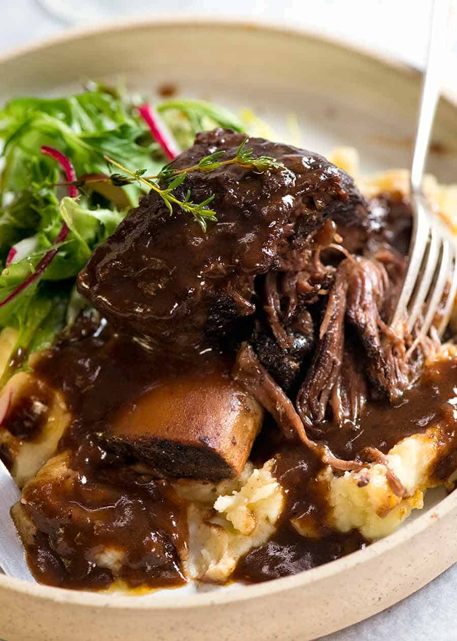 Close up of Slow Braised Beef Short Ribs in Red Wine Sauce on mashed potato on a rustic white plate, ready to be eaten