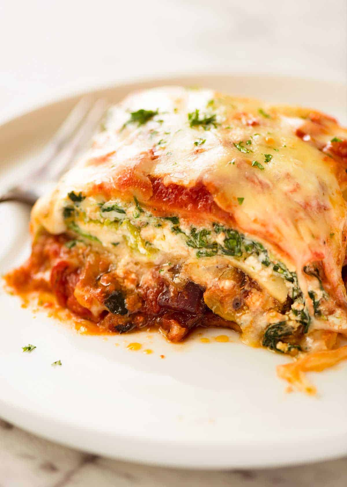 Close up of a slice of Vegetable Lasagna on a white plate, ready to be eaten