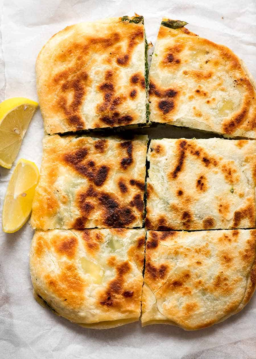 Overhead photo of Spinach and Feta Gozleme cut into 6 pieces served with lemon wedges on the side