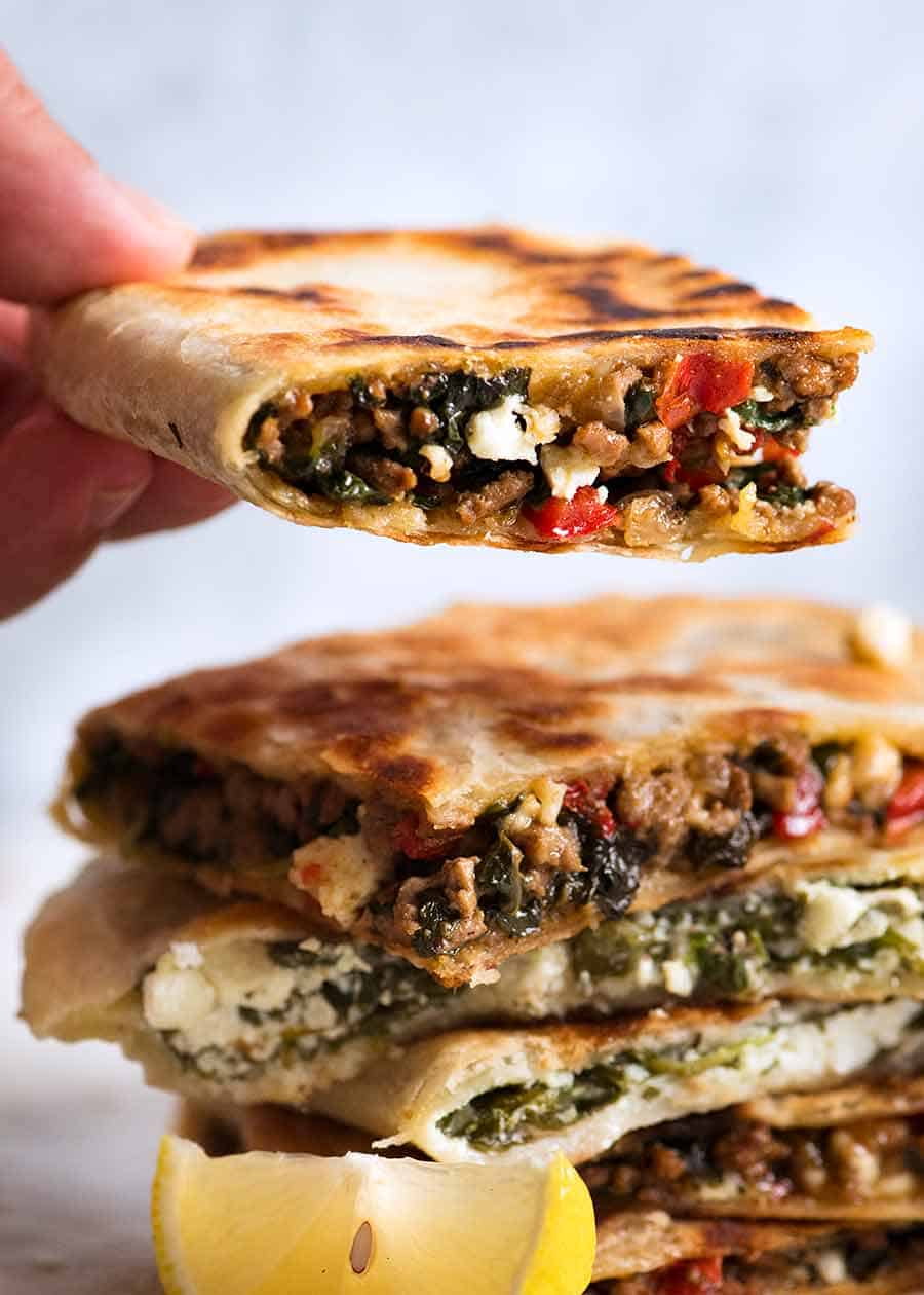 Hand holding beef and spinach gozleme