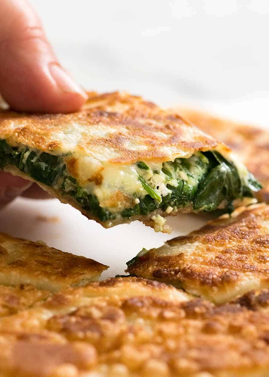 Hand picking up piece of Spinach and Feta Gozleme