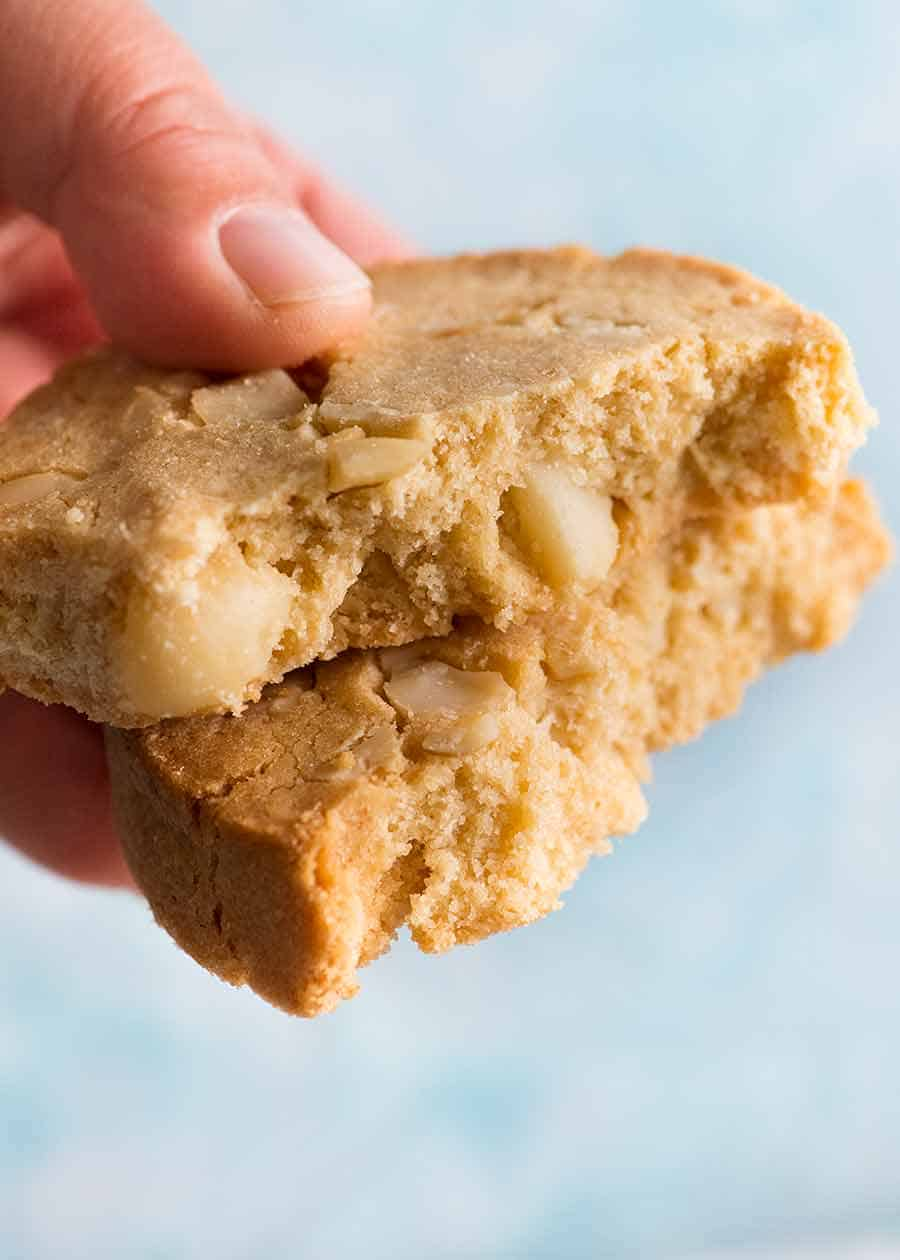 Hand holding White Chocolate Macadamia Nut Cookies broken in half to show inside