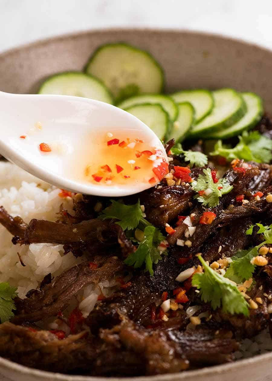 Nuoc Cham sauce being drizzled over Caramelised Vietnamese Shredded Beef