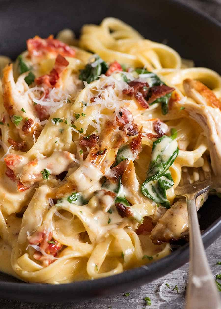 Close up of chicken pasta with creamy alfredo sauce, sun dried tomato, spinach and bacon