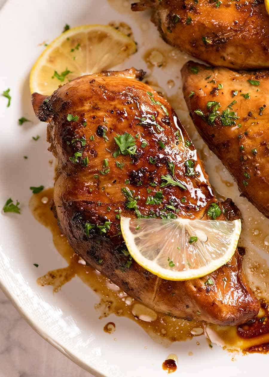 Cooked chicken breast (after marinated in Chicken Marinade) on a white plate, ready to be served