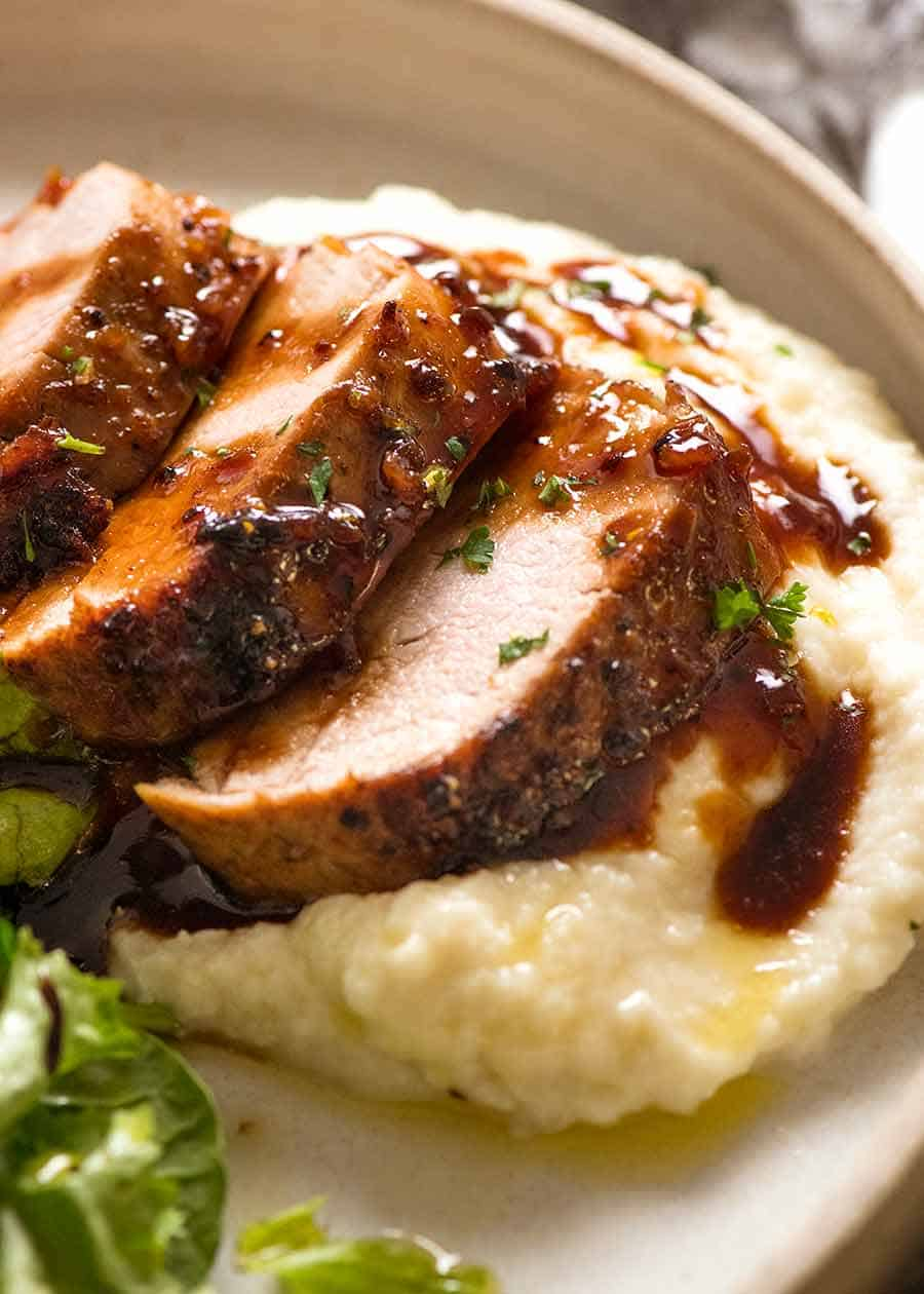 Slices of Honey Garlic Pork Tenderloin on a bed of creamy mashed cauliflower