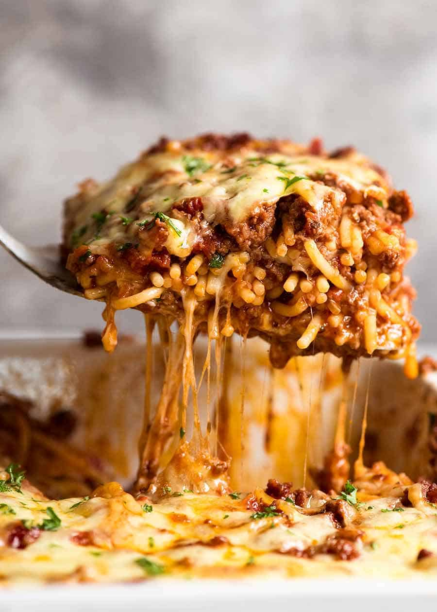 Lifting a cheesy piece of Baked Spaghetti from casserole dish