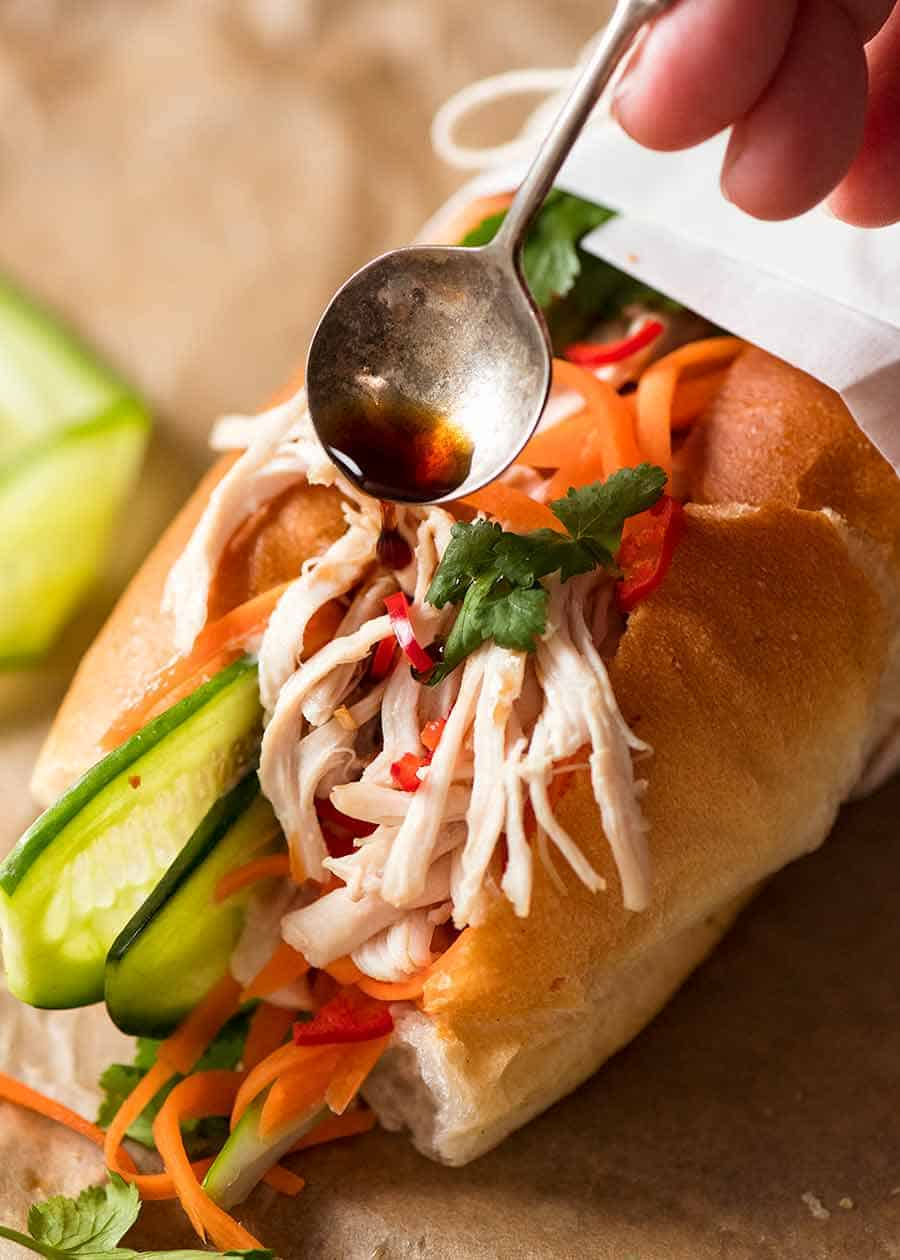 Drizzling sauce over Shredded Chicken Banh Mi