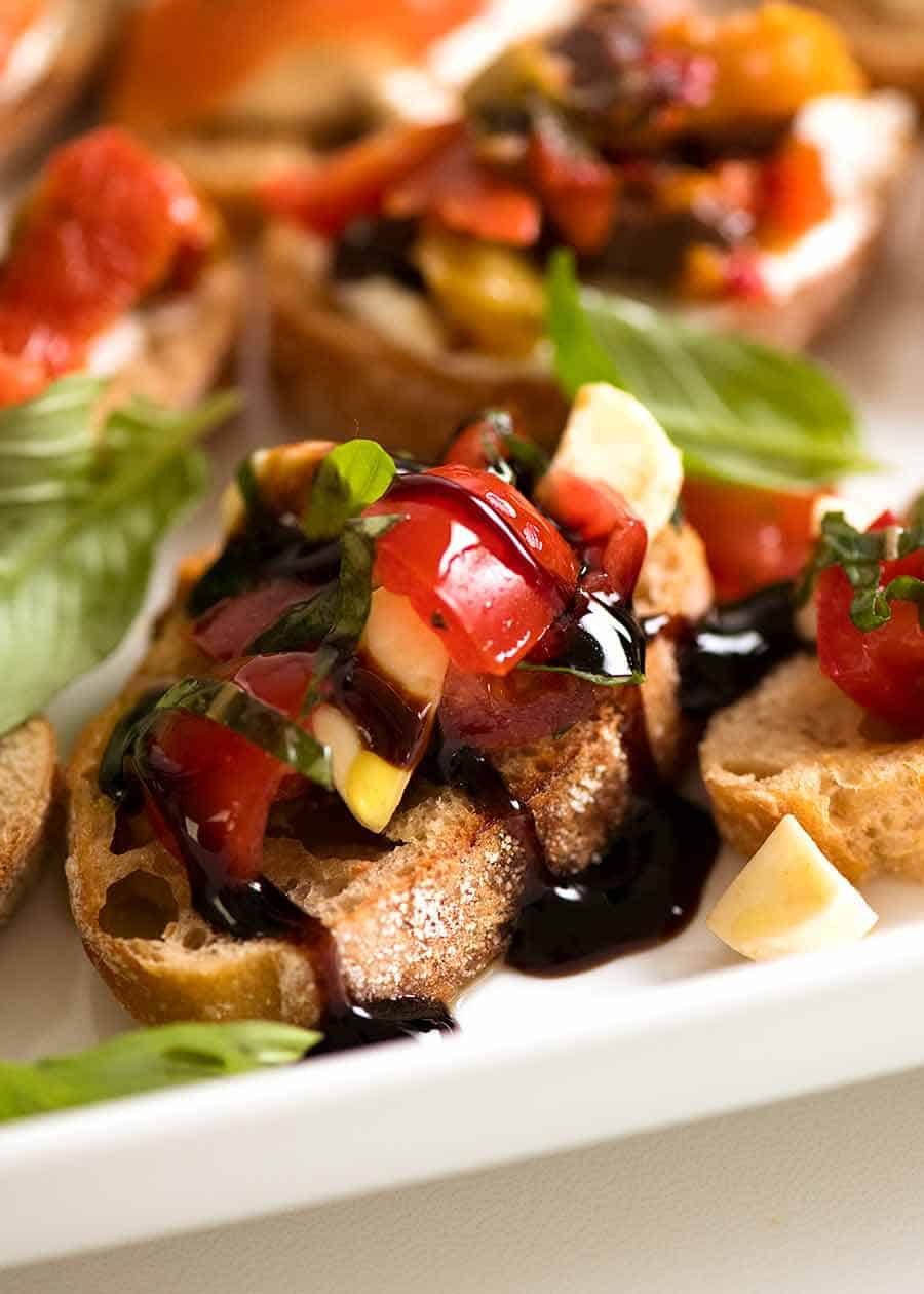 Close up of Caprese Crostini with bocconcini, cherry tomatoes, basil and balsamic glaze