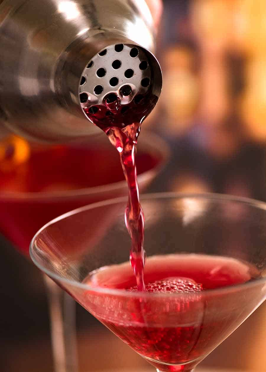 Pouring cosmo from cocktail shaker